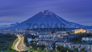 Panorama of night city of Petropavlovsk-Kamchatsky on background of volcano, urban development at twilight, backlit city road with car lights