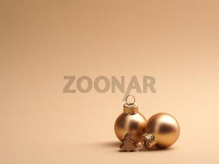 Golden vintage Christmas baubles on a beige background