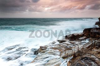 Large swells engulf the rock shelf  at sunset