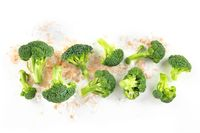 Broccoli florets, shot from above on a white background with sea salt and a place for text