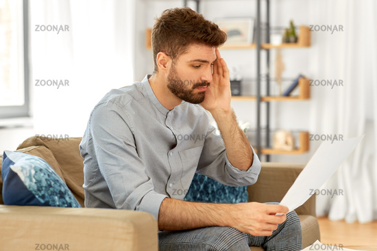 unhappy man with bills or tax report at home