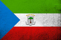 The Republic of Equatorial Guinea National flag with coat of arms. Grunge background