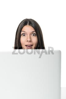 Frau schaut überrascht hinter ihrem Computer hervo