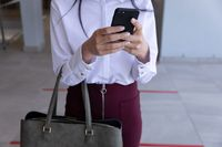 Mid section of businesswoman using smartphone