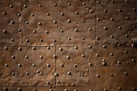 Old wall covered with sheets of rusty iron with rivets. Abstract retro background