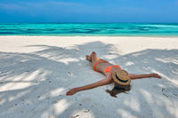 Woman in bikini at tropical beach under the palm tree