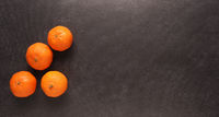 Fresh clementines on a black stone table, view from above