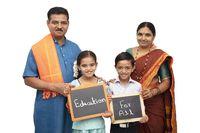 Concept of Education for all children holding slate with traditional Indian family on isolated background