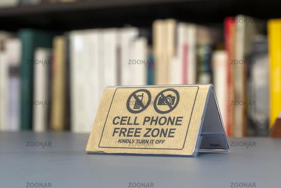 Hinweis Handyfreie Zone mit Büchern im Hintergrund - Symbolbild