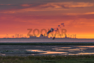 Sonnenuntergang am Watt mit Windturbinen und Industriegebäude im Hintergrund, Campen, Germany