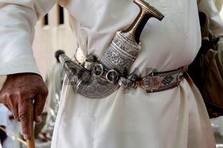 Omani man wearing a Khanjar or Jambiya, the traditional engraved silver knife, Nizwa Souk, Oman