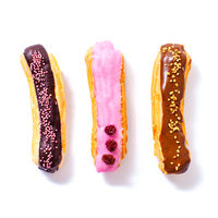 Delicious eclairs with chocolate, raspberry and caramel filling