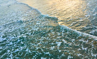 Sea surf - water surface in the evening light