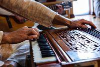 Man hands playing harmonium in room