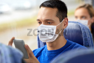 man in mask using smartphone in travel bus