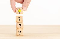 Creative idea or innovation concept. Hand picked wooden cube block with question mark symbol and light bulb icon