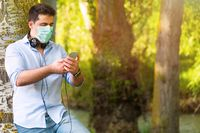 Young Man with protective face mask listening to music outdoors in the park while maintaining social distance. Lifestyle during Covid-19 pandemic outbreak.
