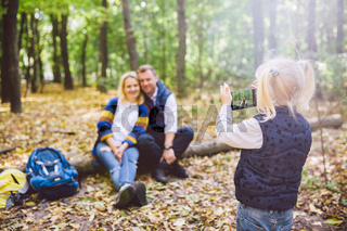 travel, tourism, hike, technology and family concept. Happy child makes photo parents in forest. Mom and dad pose for photo, daughter takes photo on phone. Young family of tourists in wooded area