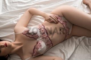 Slim female in elegant white lace lingerie