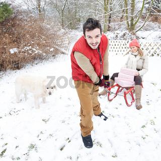 Paar zu Weihnachten mit Schlitten und Geschenken