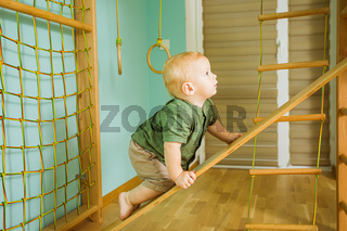 Comprehensive physical development in the gym for a toddler boy