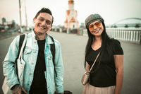 Two friendly travelers are toothy smiles looking at camera on background of the spacious city promenade. Travel concept