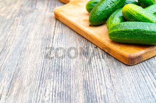 Ripe green cucumbers on cutting board for vegetables. Vegetables on kitchen table.