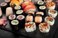 Large sushi set on a black background. Many different maki, nigiri and rolls
