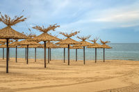 Beauty wooden umbrellas of empty sandy beach