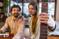 Woman hand holding guitar string with man