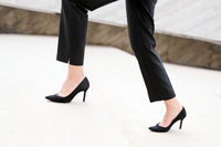 Businesswoman wearing heels climbing the Stairs in the city. Slow motion Close up on legs.