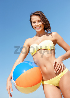 girl in bikini with ball on the beach