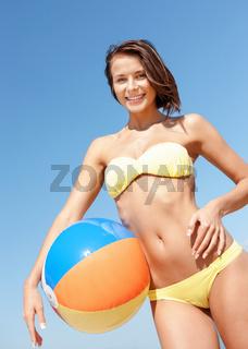 girl in bikini with ball on the beach