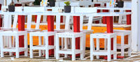 Row of colorful tables and chairs in outdoor cafe