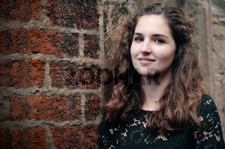 happy smiling girl leaning against old brick wall