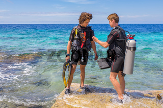 Two young divers check diving equipment in sea