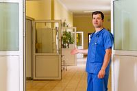 Male doctor in scrubs standing in a hospital and welcoming patients for coronavirus vaccination