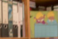 Unscharfer bunter Hintergrund eines Kinderzimmer Regales mit Ordnern und Stundenplan