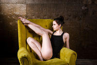 A young beautiful, sexy Caucasian woman with thin figure and long bare legs, barefoot posing reclining on yellow armchair in the interior against dark wooden wall. Dressed in a black classic swimsuit
