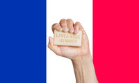 Caucasian male hand holding soap with words: Lavez-vous les mains, in French against a French flag background