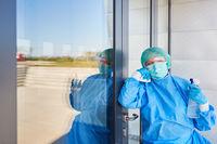 Reinigungskraft ist nachdenklich beim Desinfizieren von Klinik Eingangsbereich