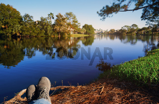 POV of man relaxing next to the lake