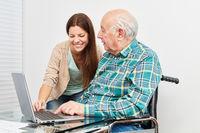 Junge Frau zeigt Senior am Computer Internet
