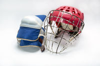 Hockey gloves,helmet and puck lay a white background isolated
