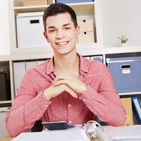 Lachender Student sitzt am Schreibtisch