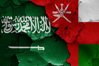 flags of Saudi Arabia and Oman painted on cracked wall