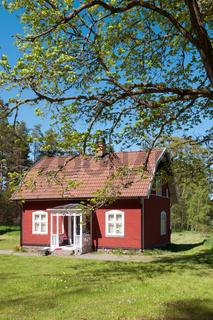Typisches rotes Holzhaus in Schweden im Frühling