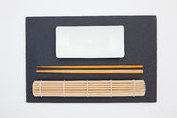 Rectangular slate plate with chopsticks, ceramic plate, bamboo mat for sushi on the white table.