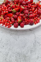 Fresh summer fruit composition. Strawberries, red currants, raspberries placed on metal tray