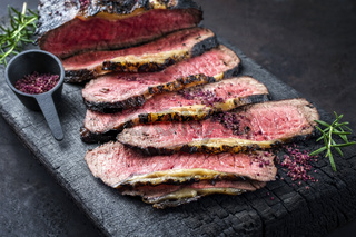 Traditional Commonwealth Sunday roast with sliced cold cuts roast beef with herbs and salt as close-up on a rustic charred wooden board